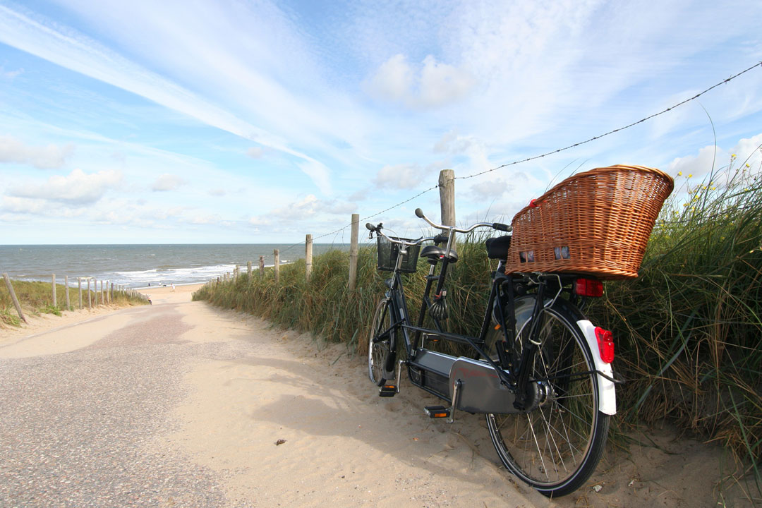 A tandem bike rest against the verge of a sandy path that leads down to the sea
