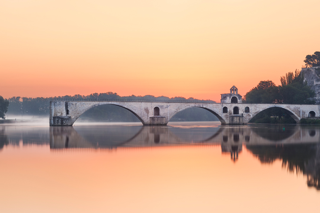 Avignon's bridge is surrounded by the tranquil river and an orange sky