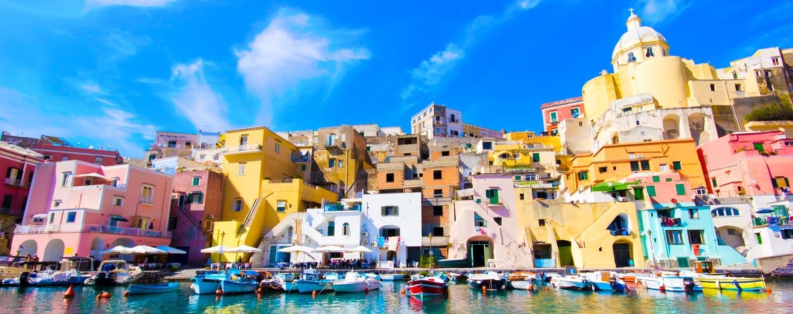A variety of dingys are harboured infront of a marina with multi-coloured flat roofed houses, typical of the Italian riviera lining the shore