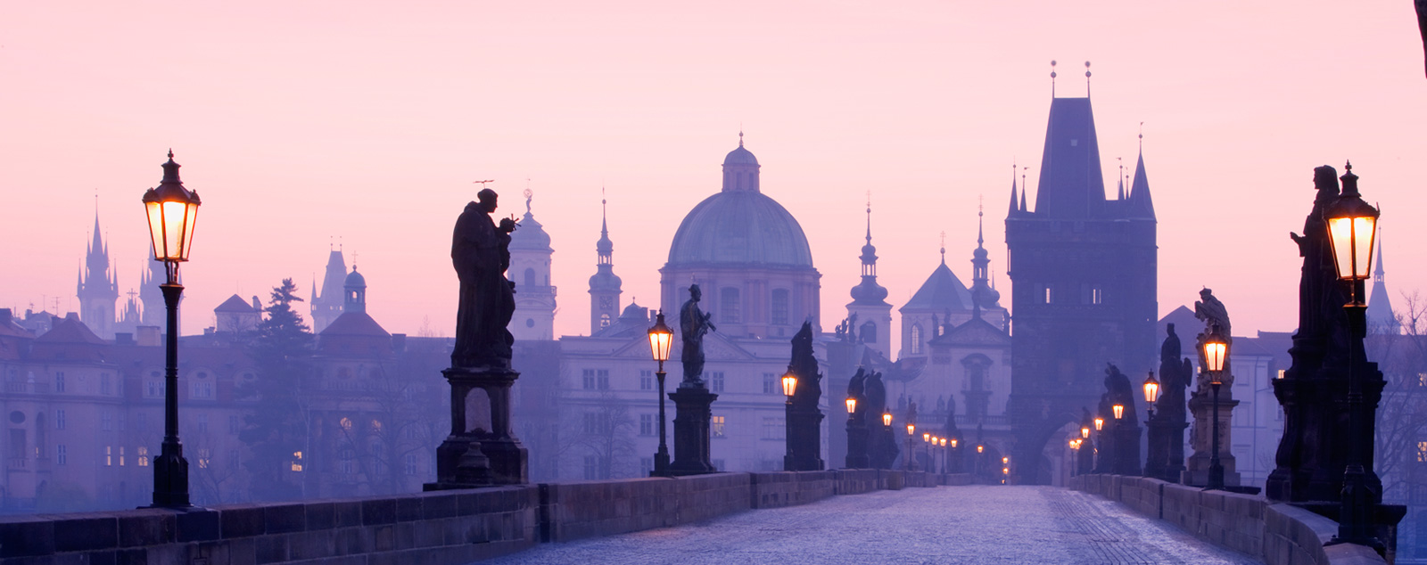 Twilight on a bridge in Prague imbues a purple haze across the towers and spires of the city
