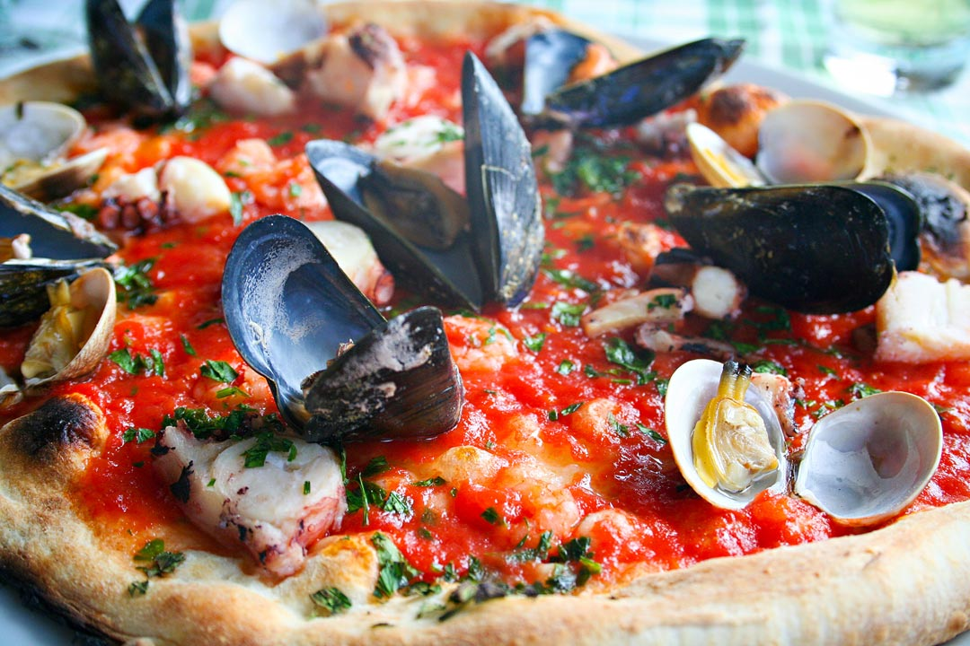 Mussels and other seafood on a pizza covered in tomato sauce
