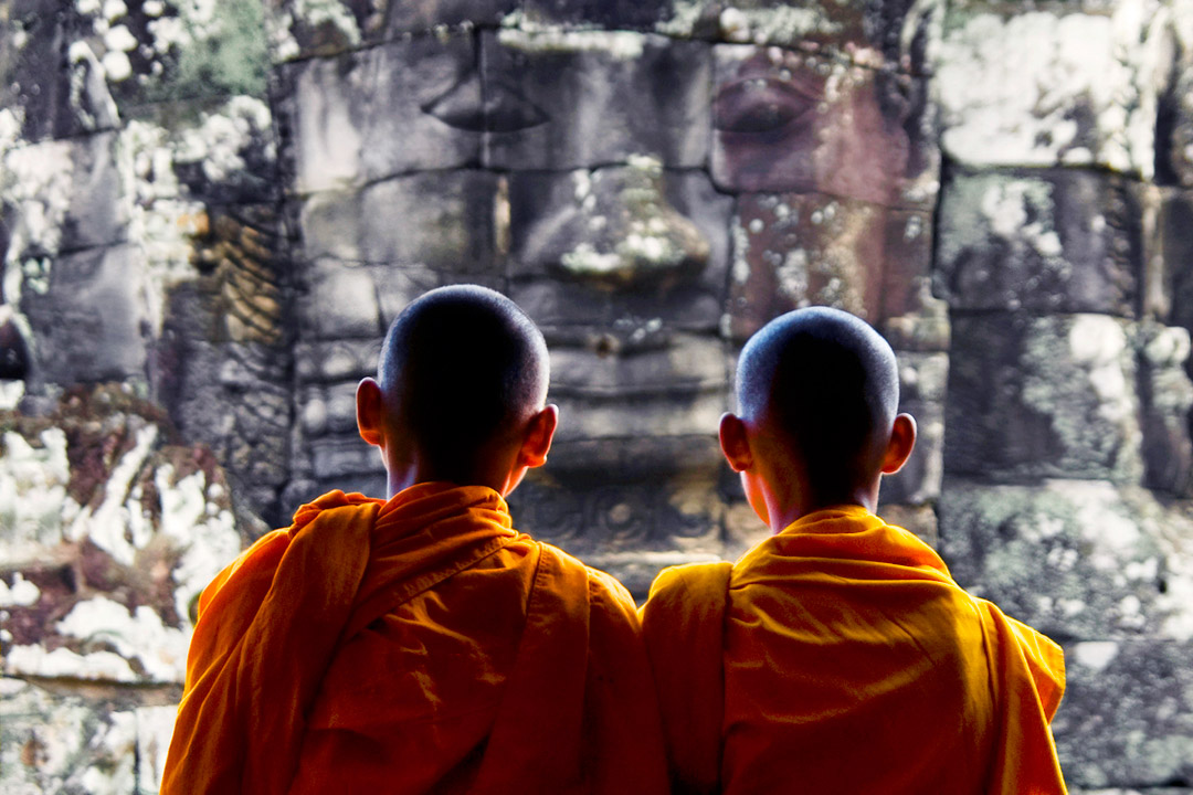 Two Cambodia child monks looking at a Khmer temple