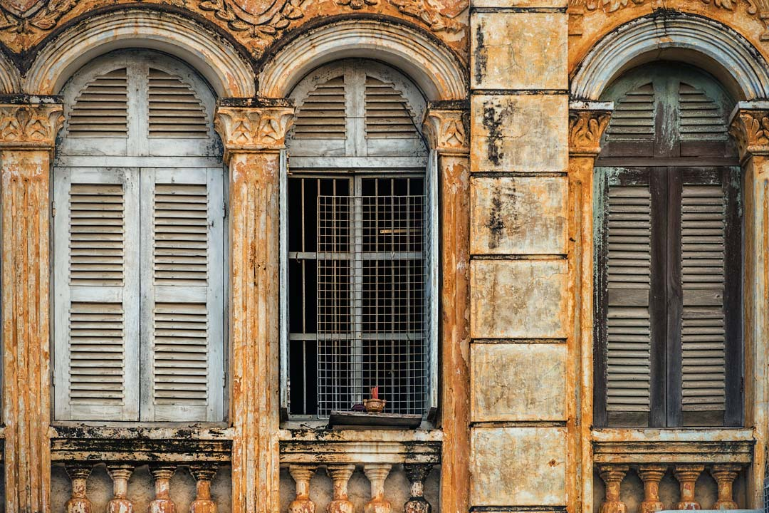 A crumbling French Colonial facade showing signs of decaying grandeur
