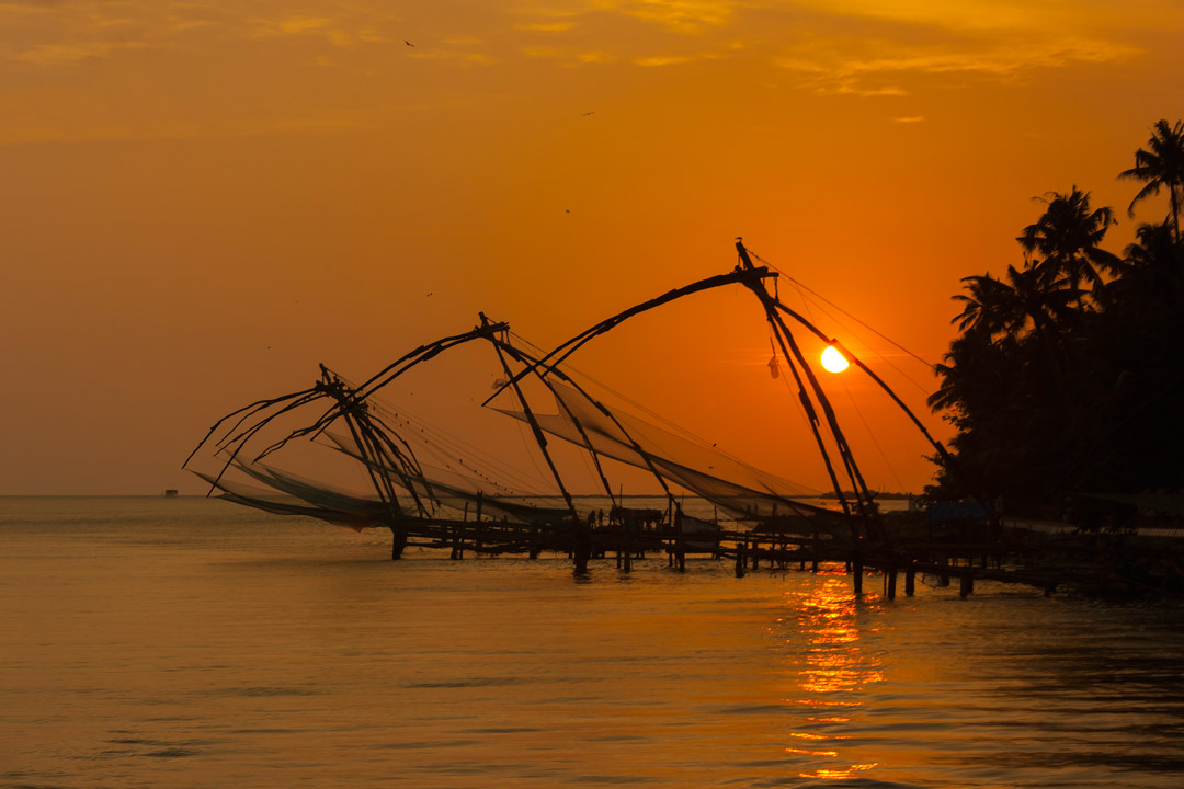 Iconic Chinese fishing nets line a bay under the glow of an orange sunset