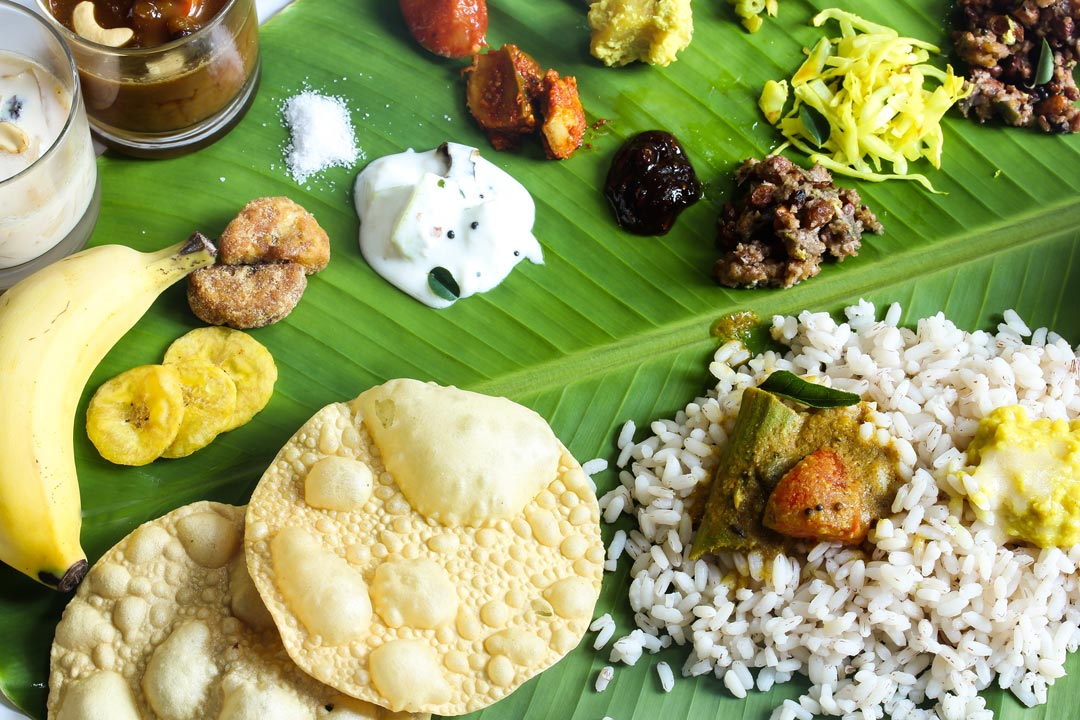 A large leaf covered in chutneys, cauces and currys alongside poppadoms and rice