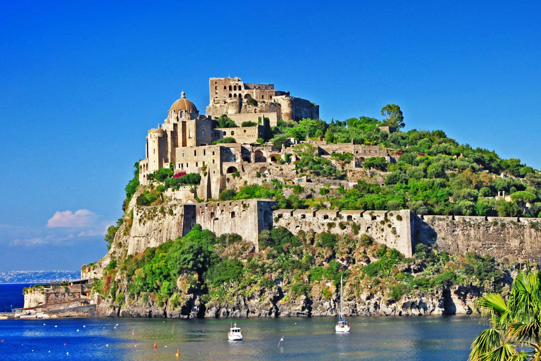 Castello Aragonese sits on a rocky outcrop jutting into the sea. It has multi-tiered stone fortifications and is surrounded by bright green trees