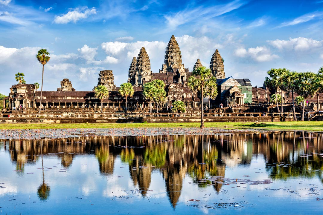 The towering spires of Angkor Wat under a blue sky and reflected in a glassy lake