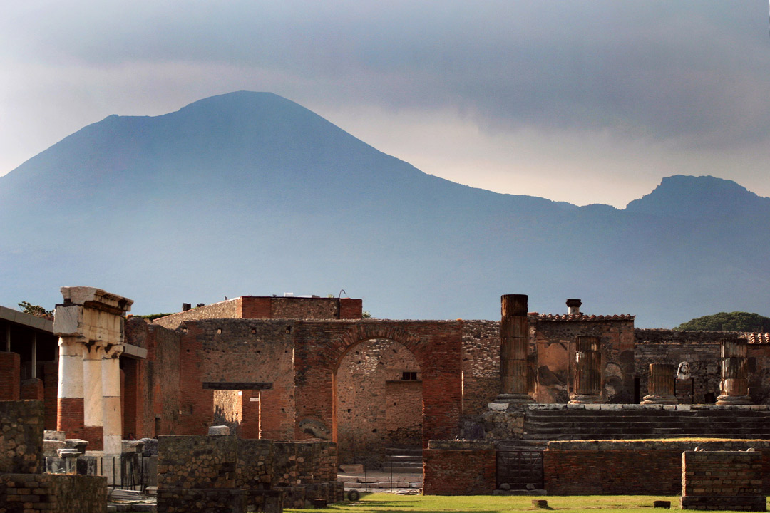 Immaculately preserved Roman ruins with the outline of Vesuvius hovering ominously in the background