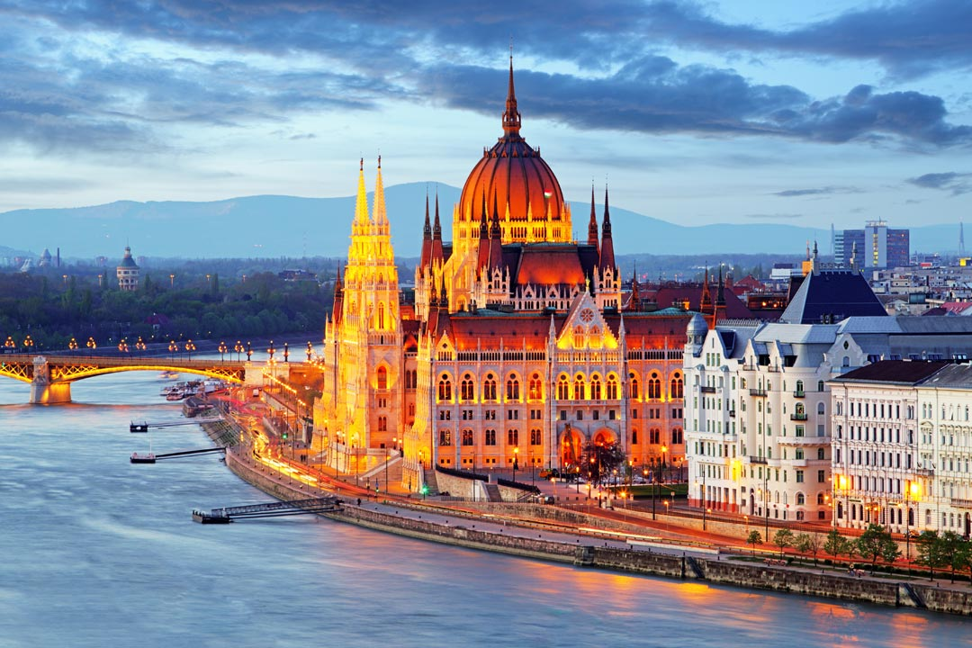 The domed gothic Hungarian parliament buildings with mutiple spires sit on the banks of the river