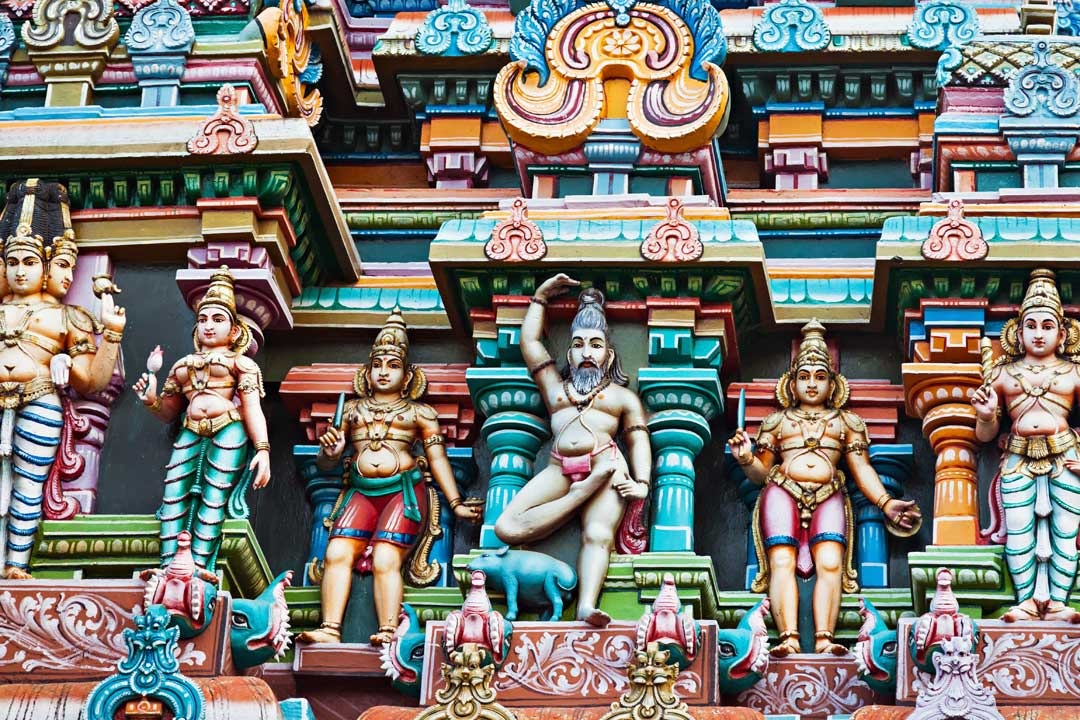 Colourful painted gods, animals and people adorn a steep temple facade