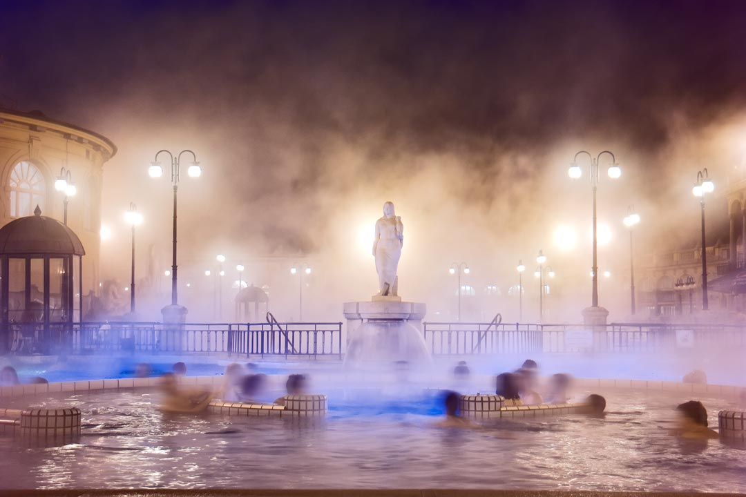 People relax in a thermal pool as a marble figure watches over in the background
