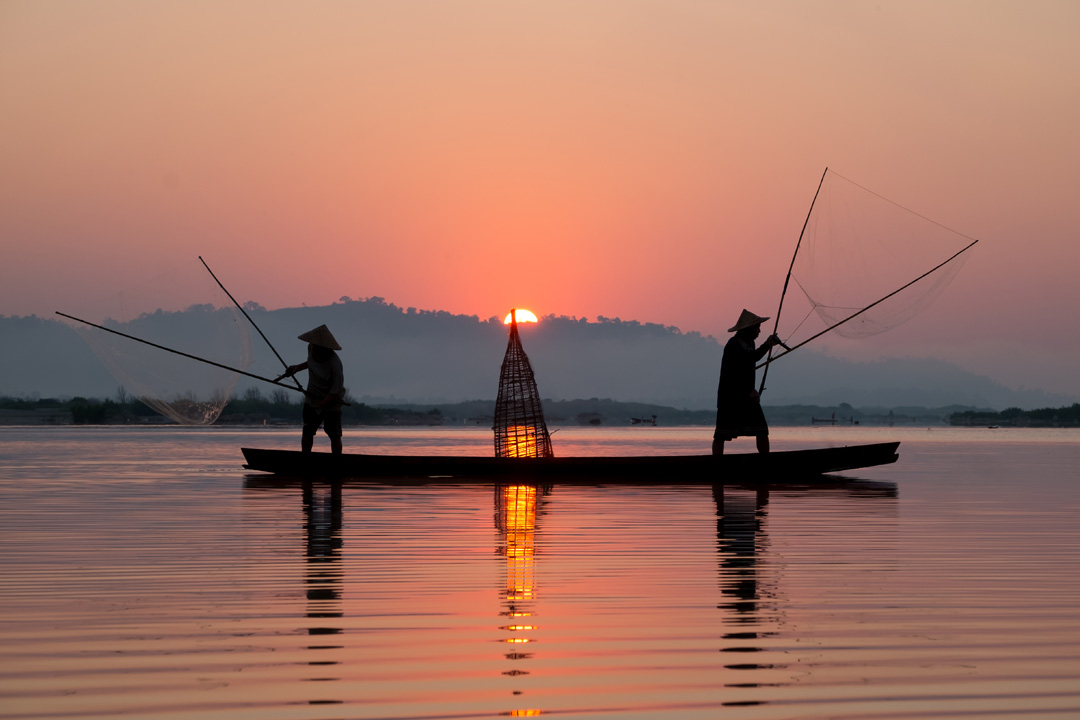two fisherman throwing fishing lines into a calm lake at sunset from a canoe