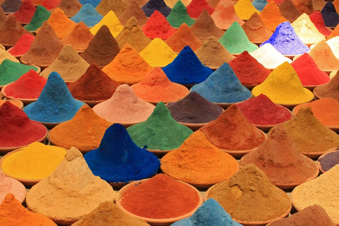 multiple pots holding pyramids of exotic coloured spice powers in a market