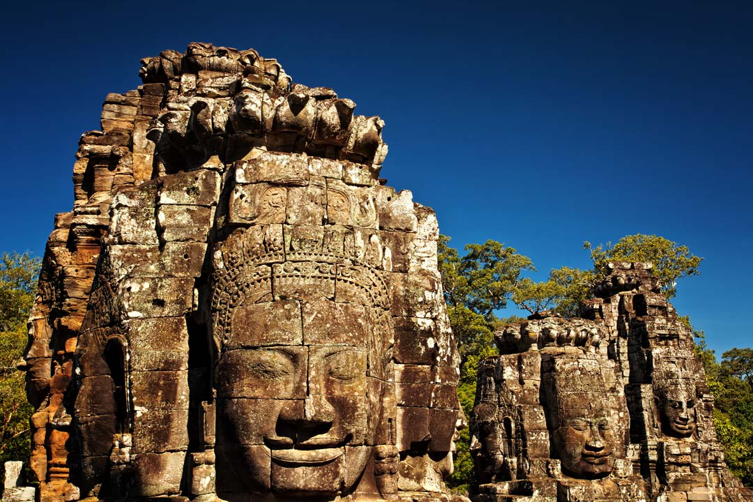 Colossal stone faces carved into temple towers