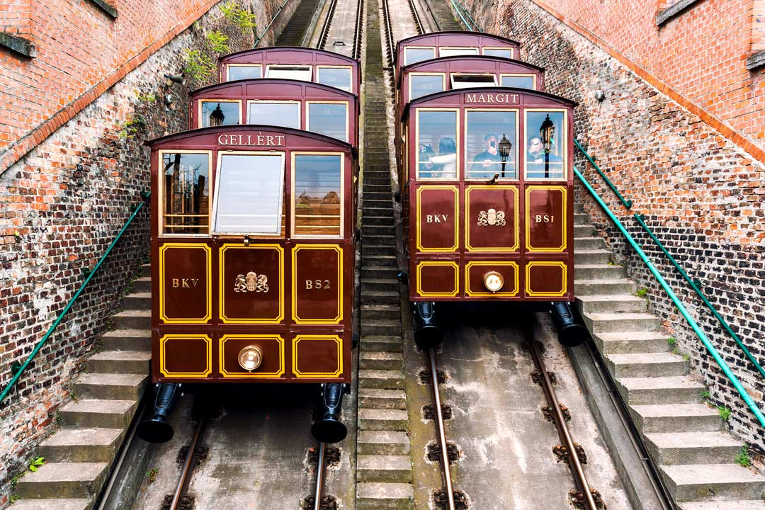 Two funicular railway carriages pass each other with stone walls on either side