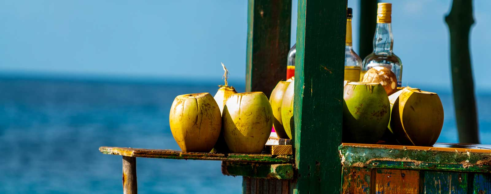Many coconuts and bottles of rum sit on a colorfully painted wooden bar