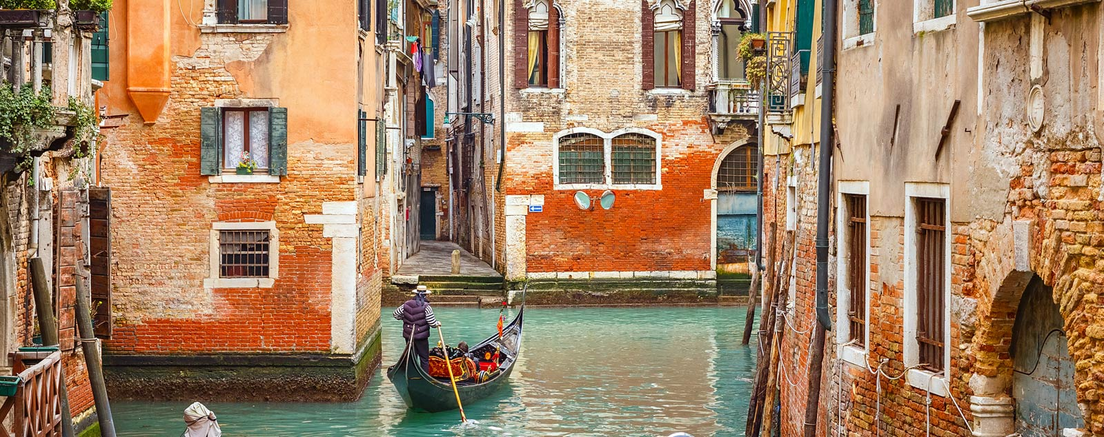 A gondola cruises between Venice's narrow waterways and typical red brick houses