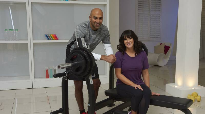 Amar leaning on a weight bench with Anna Richardson, fellow presenter on 'How to Get Fit Fast'