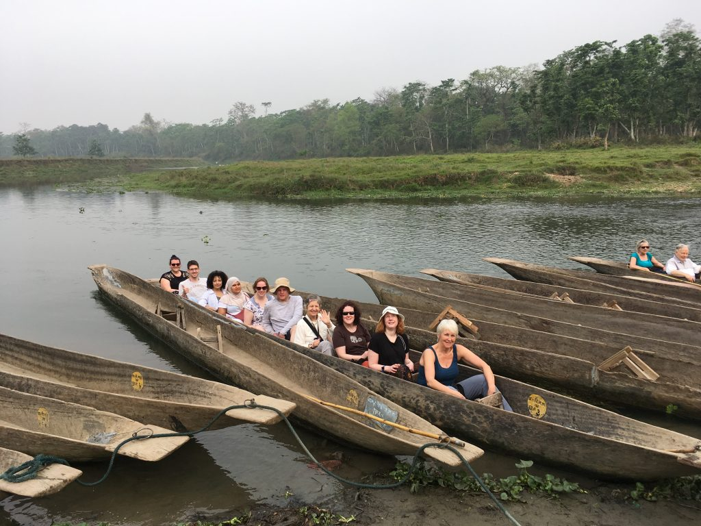 Members of the group are embarking on a 15 meter long dugout canoe, in front of a lush rain forest.