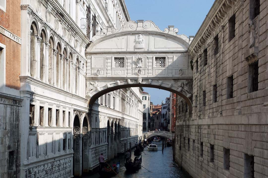 A narrow waterway is filled with gondolas and has stone walls on either side with an ornate arch overhead