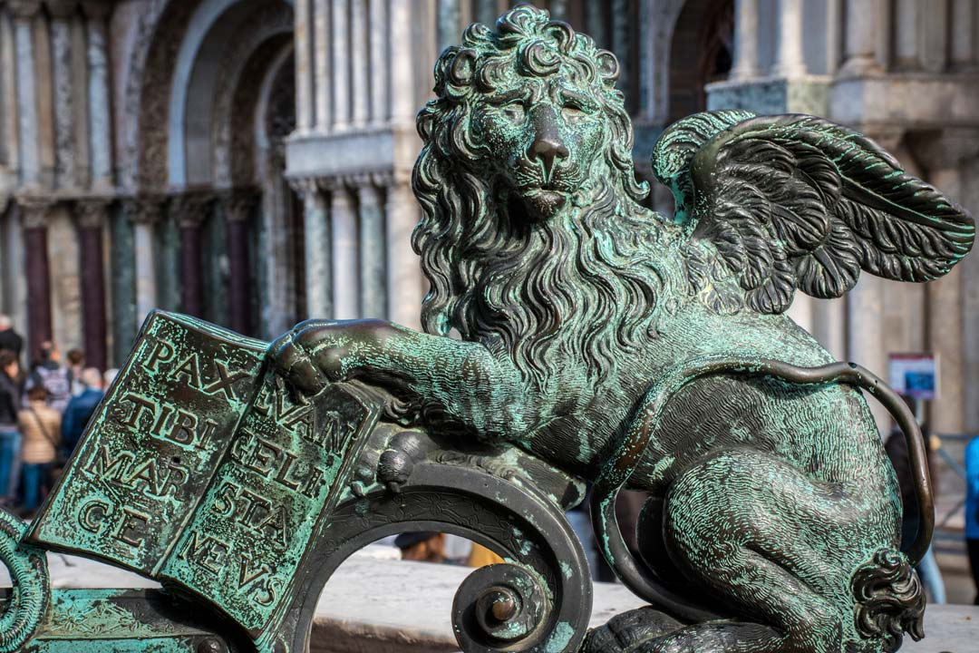 An iron Venetian lion holding a book with Latin enscriptions