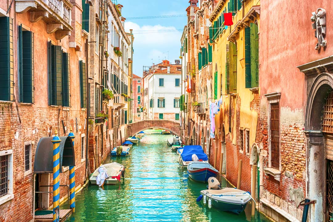 A narrow waterway with pastel houses, covered motorboats and washing hanging down from the windows