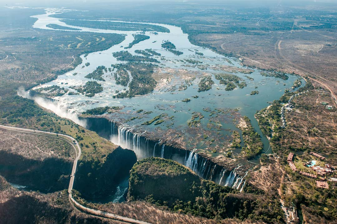An aerial view of Victoria Falls,. The wide Zambezi meanders and flows into the a deep gorgewith the falls crashing down into it and creating white spray