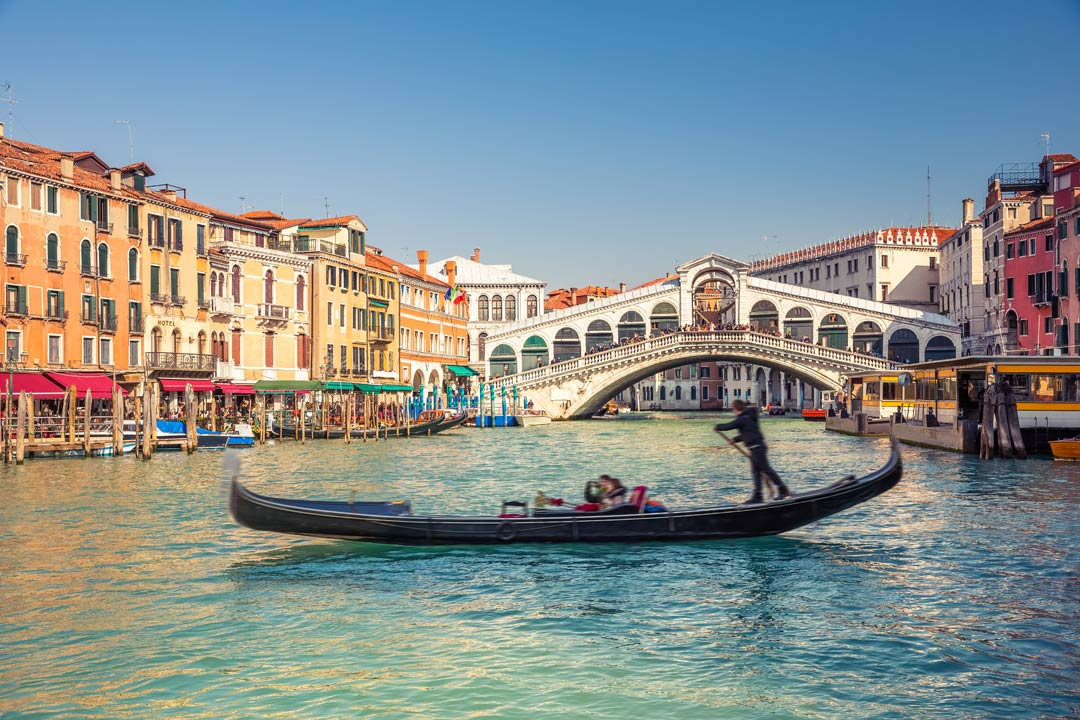 A gondola in the foreground, a spectacular white orante bridge is behind with multiple archways