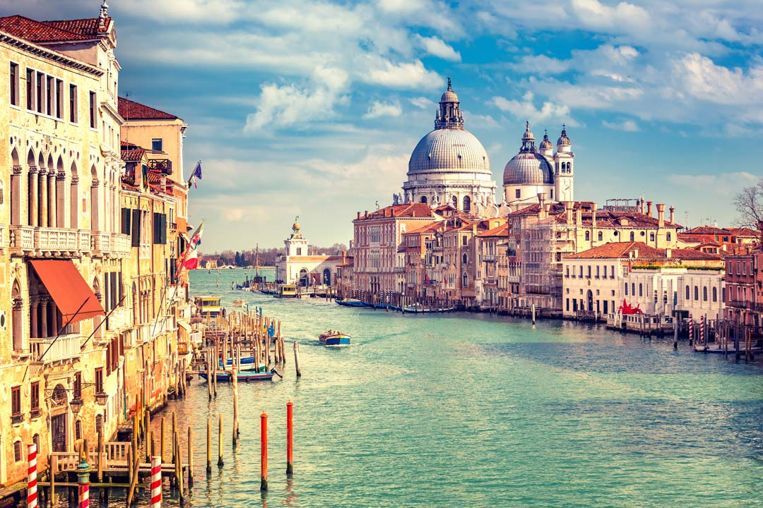 Venice's grand canal lined on either side by traditional pastel houses. In the background is two of Venice's vast domed churches