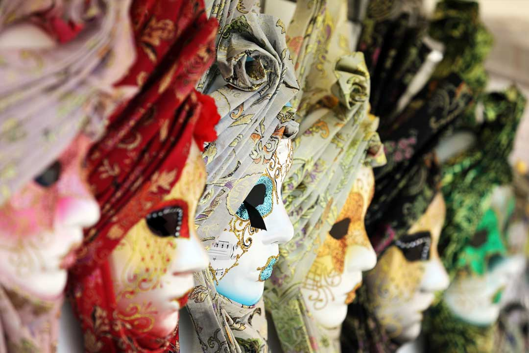 Typical Venetian masks, multicoloured with ornate patterns on the face and head scarf