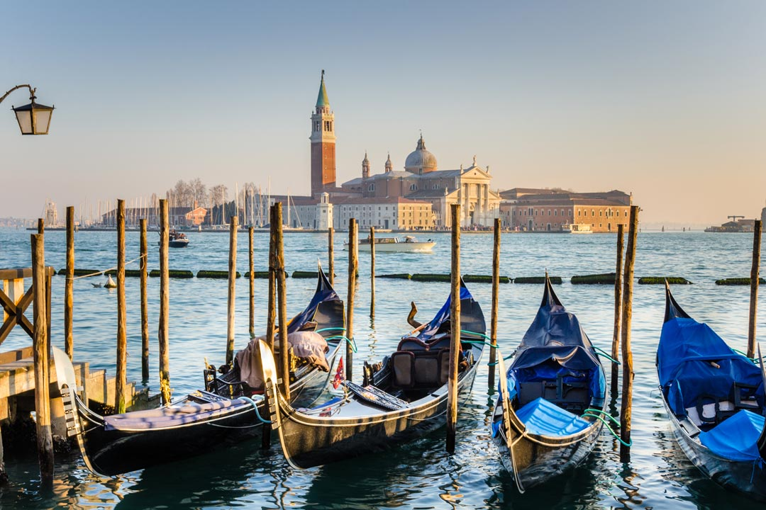 One of Venice's open waterways, gondolas are moored between wooden poles. In the background are white palatial buildings, including a dome and a tower