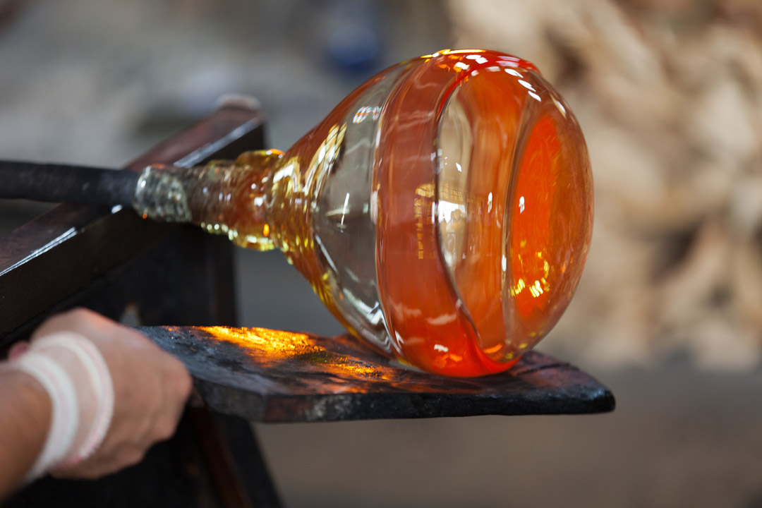 Traditional murano glass blowing, over a molten hot metal board