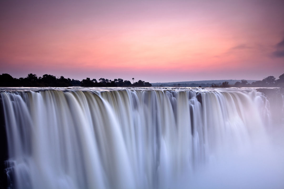 The Victoria falls pour steeply down creating a haze of spray