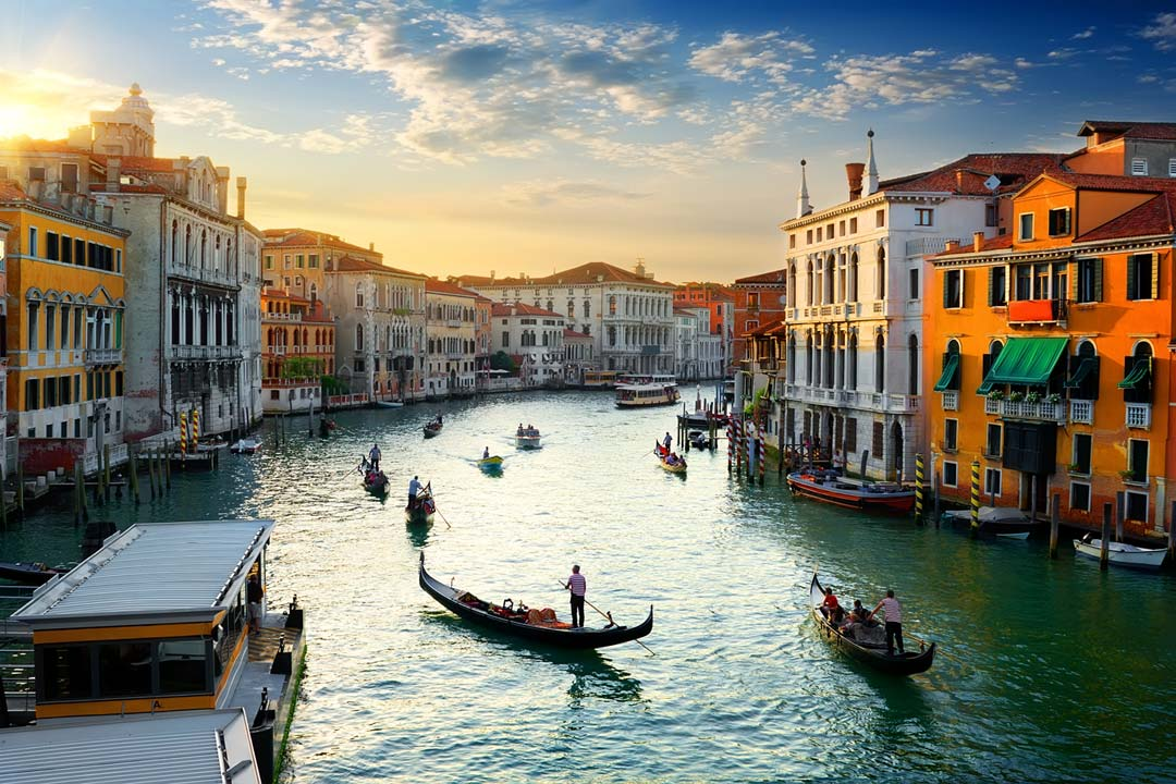A sunset over Venice's traditional rooftops, with multiple boats sailing gently along the canal