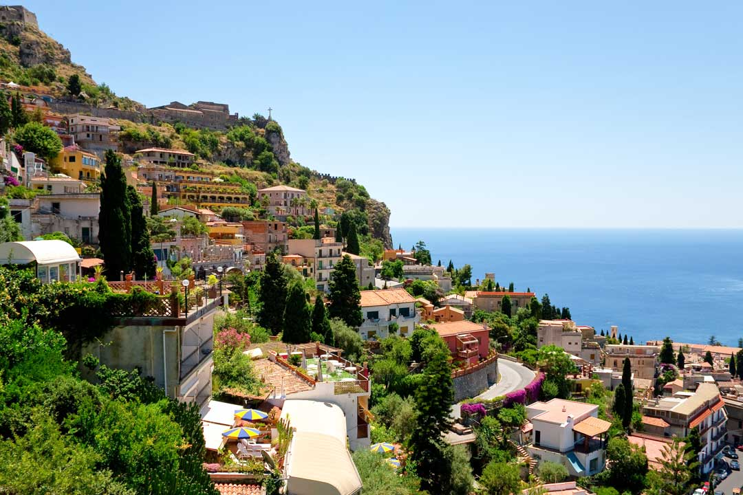 Typical Sicilian buildings spread down a cliff side to the pure blue Mediterranean sea