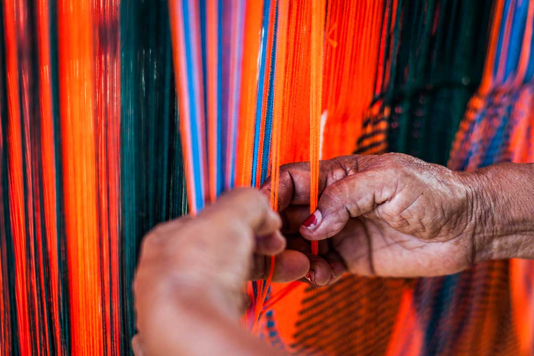 Hands are feeling orange and blue coloured thread