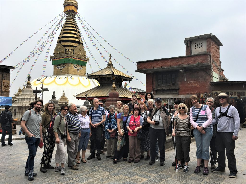 Our group holiday at Swayambhunath - the Monkey Temple - in Kathmandu! They are standing in front of a temple spire, adorned with colourful bunting.