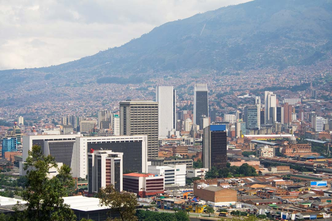 Medellin's skyline, dominated by tall modern buildings. A hill rises in the background, forming one edge of the valley Medellin sits in