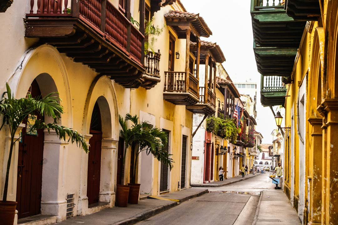 A traditional street, with potted palm trees and pastel coloured houses with wooden balconies facing inwards