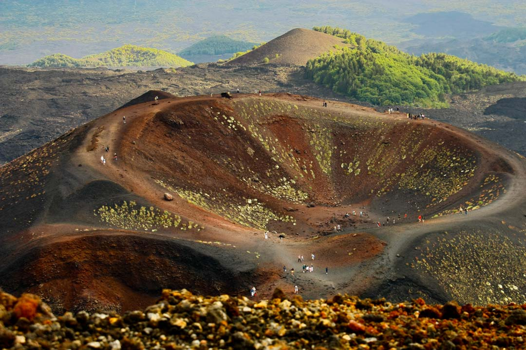 One of Etna's giant circular craters, with green trees on the hills behind