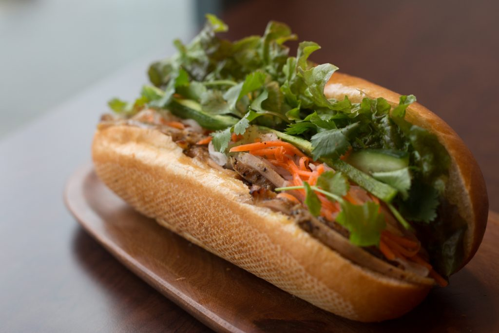 A healthy sub sandwich / Vietnamese banh mi filled with meat and healthy vegetables.