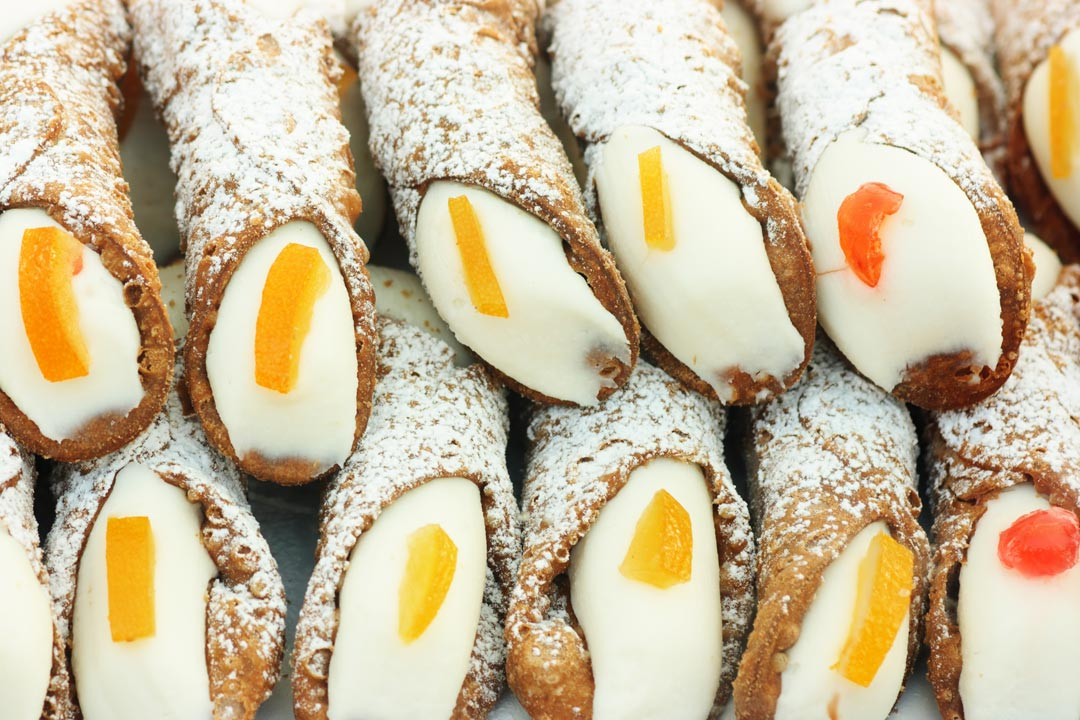 Sicilian cannoli, crisp pastry is stuffed with a creamy filling with pieces of fruit stuck on