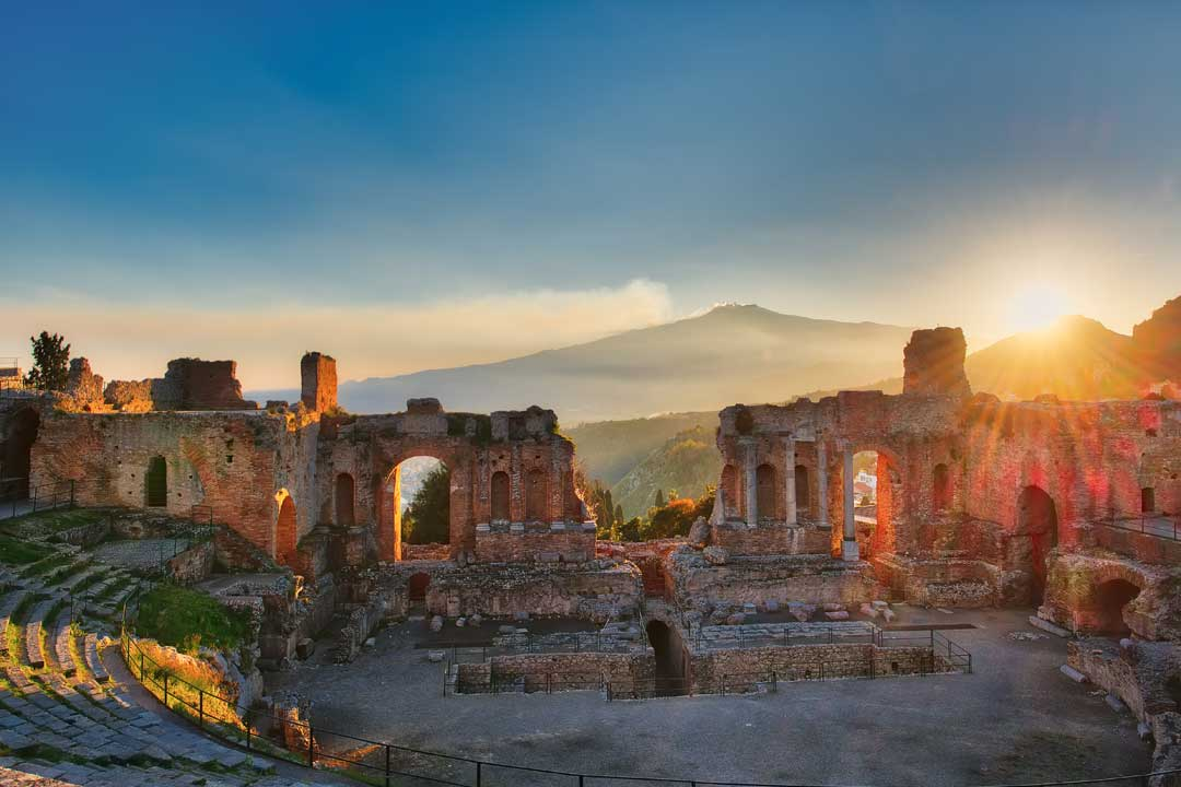 Taormina's ancient Greek theatre perfectly framing Etna and the sun setting behind it.