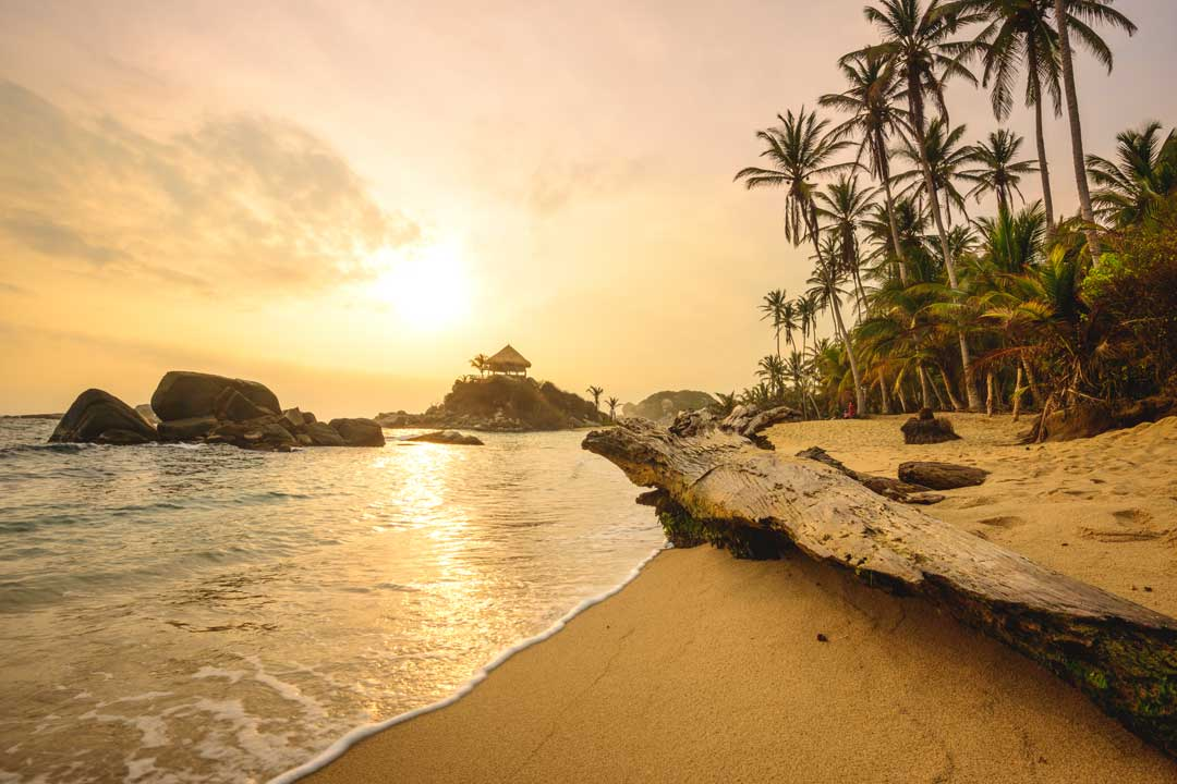 The sun sets over a rock formation sticking out into the sea. A beach is covered in palm trees and golden sand.