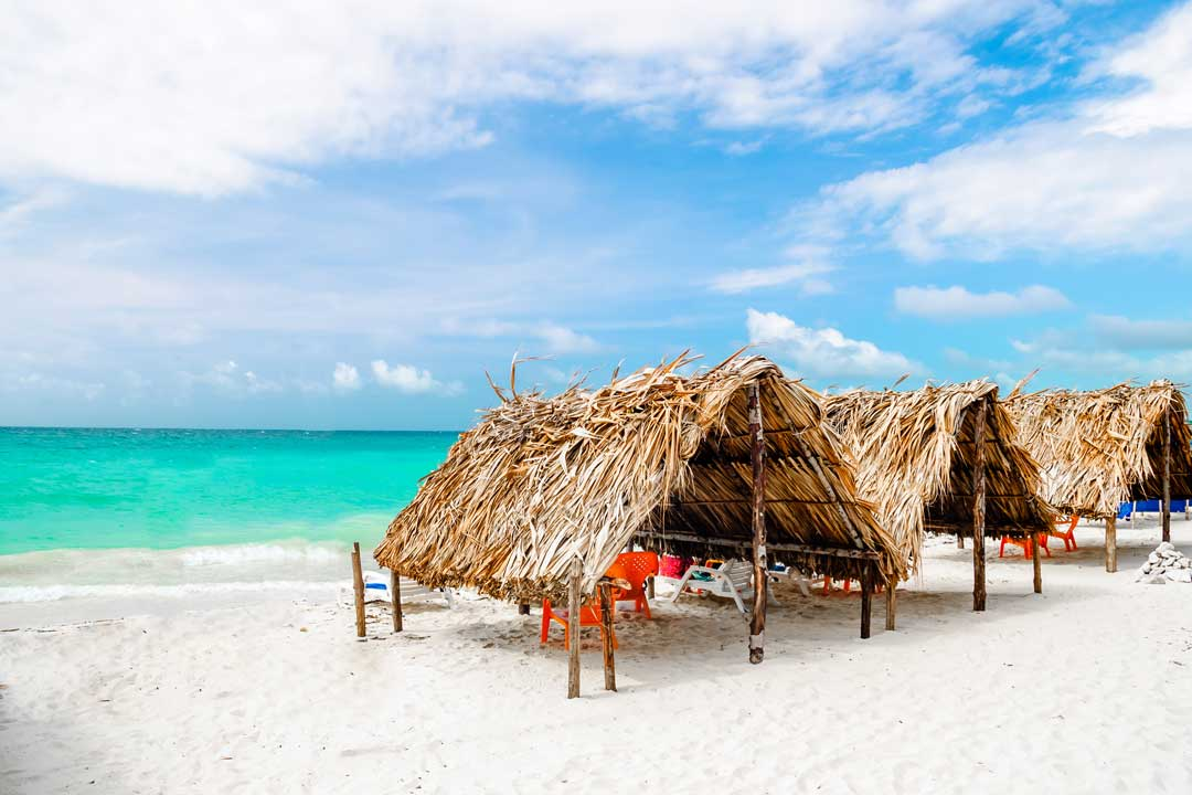 Beach shelters made of wooden beams sit on a sandy white beach