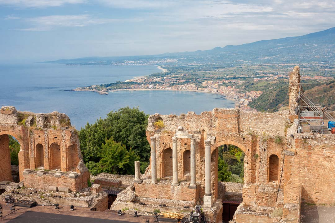 The Greek ruins of Taormina, the coast stretches off into the background with Etna rising in the distance