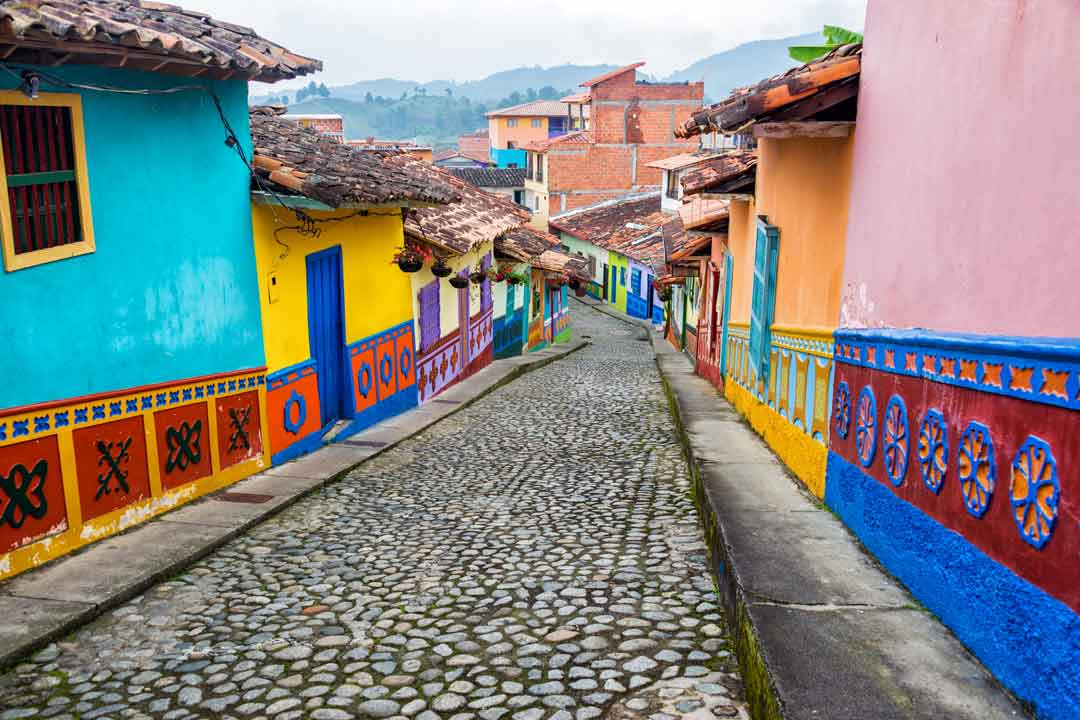 A cobbled street slopes down among brightly painted homes and tiled roofs