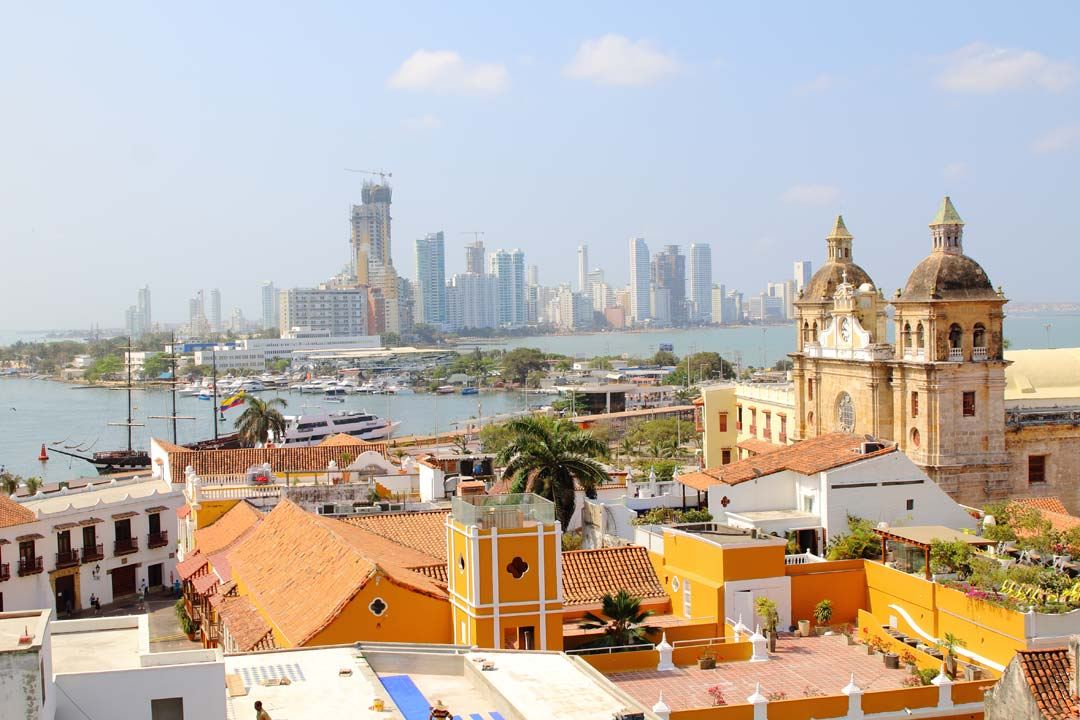 Nestled in the foreground are orange houses with tiled roofs, palm trees, and a large church with two ornate towers and a clock-face on top of a decorative facade. In the background is the harbour with old fashioned and modern ships. In the far distance towering skyscrapers show a different side to the city.