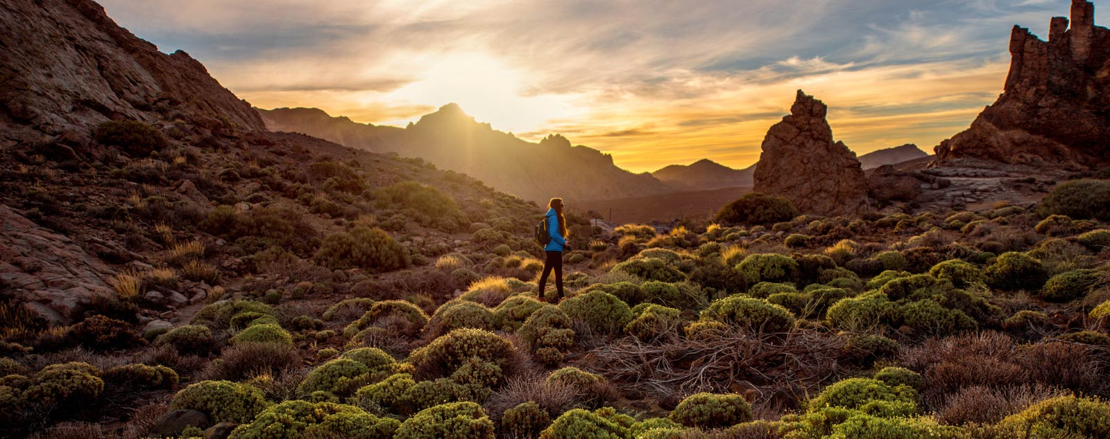 A woman walking through shrubland and rocky terrain under a yellow sunset