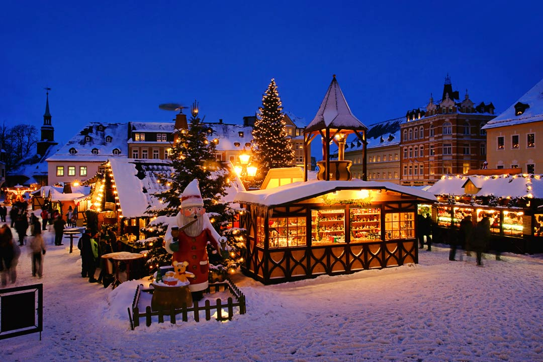 Traditional Christmas market stalls covered in snow and lit with illuminations